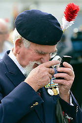© Licensed to London News Pictures. 18/10/2012. Westminster, UK A man uses a magnifying glass to read his mobile phone. Members past and present from the 2nd Battalion of The Royal Regiment of Fusiliers march on Parliament today 18 October 2012 to hear a debate in the House on the future of their regiment. The regiment's existence is threatened by the governments plans to reduce the armed forces by 20,000 personel. Photo credit : Stephen Simpson/LNP