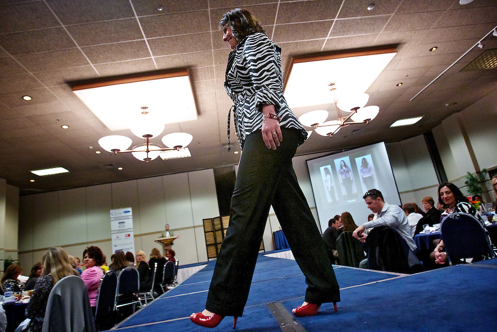 Rebecca Welsh struts on the catwalk for the crowd in her red high-heeled shoes as the story of her makeover is shared with attendees at the Women's Council of Realtors style show Thursday.