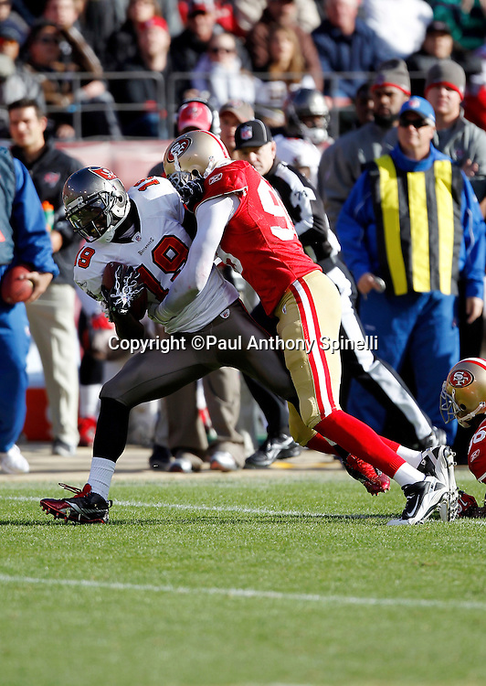 Tampa Bay Buccaneers wide receiver Sammie Stroughter (18) gets tackled after catching a pass by San Francisco 49ers linebacker Manny Lawson (99) during the NFL week 11 football game on Sunday, November 21, 2010 in San Francisco, California. The Bucs won the game 21-0. (©Paul Anthony Spinelli)