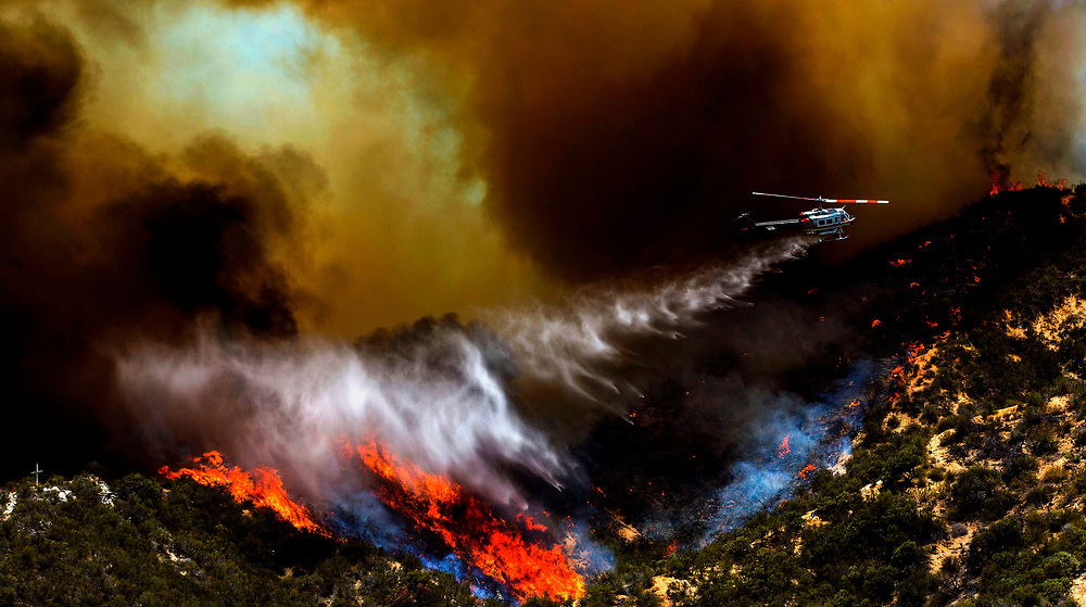 A helicopter makes a water drop onto a wildfire, Friday May 31, 2013, near Castiac, California. Fourteen aircraft and more than 550 firefighter were deployed in a ground and air campaign against a brush fire that has blackened about 1,500 acres in sparsely populated San Francisquito Canyon in the Angeles National Forest northeast of Santa Clarita. The Powerhouse Fire, which broke out Thursday afternoon, was about 15 percent contained. The estimated date of full containment is Wednesday, June 5.