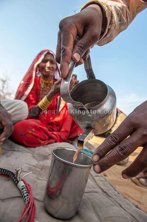 Chai tea is poured into a metal cup in the desert near Pushkar, India.