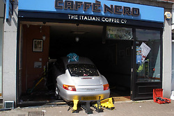 © London News Pictures. 16/05/2015. The scene where a Porsche car crashed in to a Cafe Nero coffee shop in Gerrards Cross in Buckinghamshire, UK. The driver was treated for minor injuries and a man and woman were temporarily trapped inside the shop. Photo credit: BucksFire/LNP