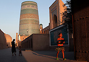 Low angle view of a young girl passing through the Ota Darvoza gate, Khiva, Uzbekistan, pictured on July 7, 2010, in the late afternoon light of a summer day with the Muhammad Aminkhan Madrasah and Kalta Minor in the background. Khiva's old city, Ichan Kala, is surrounded by 2.2 kilometres of crenellated and bastioned city walls. Some sections may be 5th century, but the strongest sections were built 1686-88 by Arang Khan. The main gate today is the restored western Ota Darvoza (Father Gate). The Kalta Minor or Short Minaret was commissioned by Mohammed Amin Khan in 1852 to stand 70 m. high, but was abandoned when he died in 1855, and remains only 26 m. high. Khiva, ancient and remote, is the most intact Silk Road city. Ichan Kala, its old town, was the first site in Uzbekistan to become a World Heritage Site(1991). Picture by Manuel Cohen.
