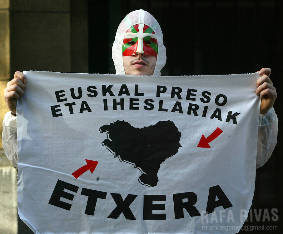 "A man masked with a Basque flag holds a banner that reads ""Basque prisoners and people with reprisals, back home"" during a protest called by the separatist armed Basque group ETA imprisoned members' relatives association 04 December 2006 in front of ruling Spanish Socialist Party-PSOE headquarters in the northern Spanish Basque city of Bilbao. PHOTO RAFA RIVAS"