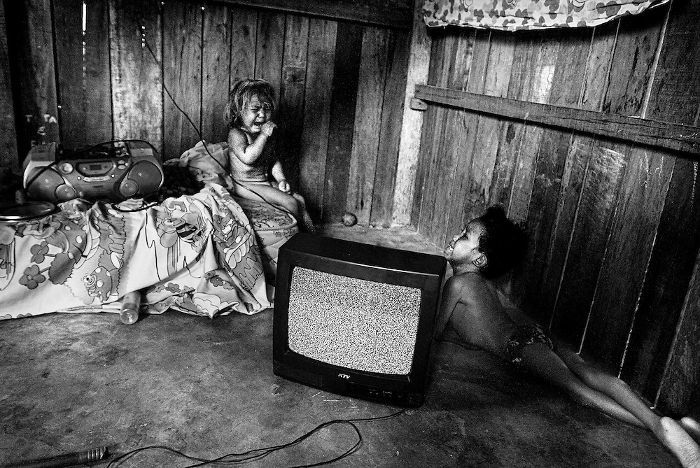 BRAZIL, SANTAREM. NOVEMBER 2008. Two children, one of them disabled (right), crying in their home after being abandoned by their mother who escaped after stabbing her partner. Most of the soya displaced families have to live in slums.