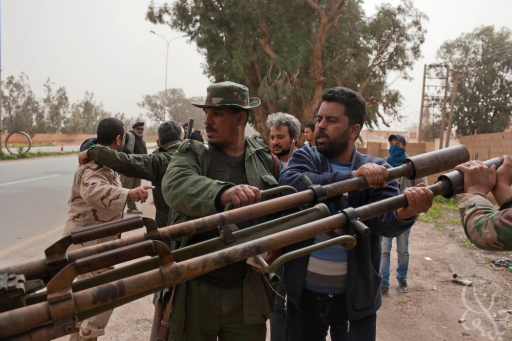 Libyan opposition fighters push an anti-aircraft gun into position at a checkpoint on the outskirts of Benghazi, Libya March 02, 2011. Fighters from the city are on alert following pro-government force offensives in the eastern Libyan cities of Berega, and Ras Lanuf. .Slug: Libya.Credit: Scott Nelson for the New York Times