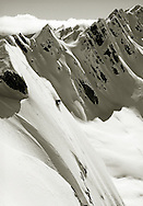 Sport. Male skier turning on steep mountain slope with mountain back drop, heliskiing, New Zealand