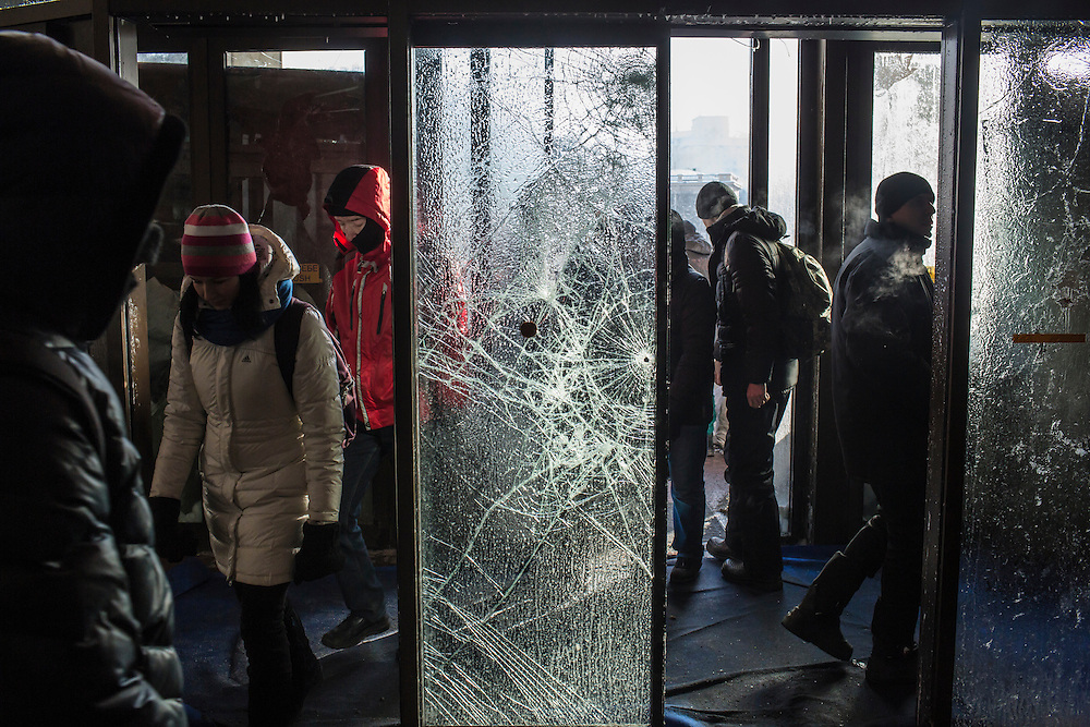 KIEV, UKRAINE - JANUARY 26: People walk past broken glass doors at Ukrainian House, which was taken over by anti-government protesters, on January 26, 2014 in Kiev, Ukraine. After two months of primarily peaceful anti-government protests in the city center, new laws meant to end the protest movement have sparked violent clashes in recent days. (Photo by Brendan Hoffman/Getty Images) *** Local Caption ***