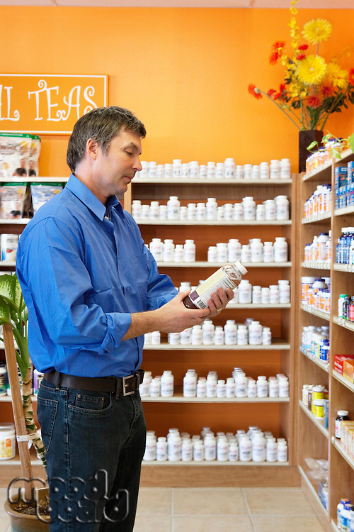 Side view of a mature man looking at pill bottle in drugstore
