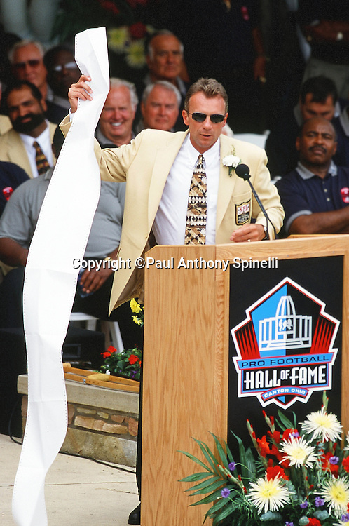 Former Former San Francisco 49ers quarterback Joe Montana holds up a long sheet of paper as he speaks at the podium during the NFL Pro Football Hall of Fame Induction Ceremony on July 29, 2000 in Canton, Ohio. (©Paul Anthony Spinelli)