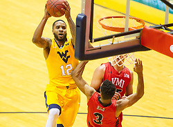 Dec 10, 2016; Morgantown, WV, USA; West Virginia Mountaineers guard Tarik Phillip (12) shoots in the lane over Virginia Military Keydets guard Adrian Rich (3) during the first half Keydets at WVU Coliseum. Mandatory Credit: Ben Queen-USA TODAY Sports