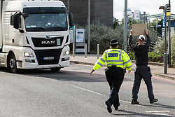 London, UK. 5 September, 2019. A Metropolitan Police officer pursues an activist walking across the road in front of a truck outside ExCel London on the fourth day of a week-long carnival of resistance against DSEI, the world's largest arms fair.