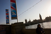 A Muslim lady tourist walks along the Embankment past Parliament under Conservative election banner.