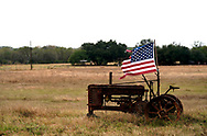 A tattered U.S. flag flies on an old tractor in a farm field outside Sutherland Springs, Texas, U.S. site of the First Baptist Church shooting November 8, 2017.  REUTERS/Rick Wilking