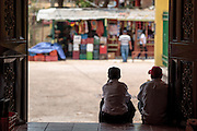 Two men sit on the steps of the local market in the town of Valle de Angeles, Honduras on Friday April 26, 2013.