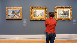 Visitor looking at paintings by Alfred Sisley  at new Museum Barberini in Potsdam Germany