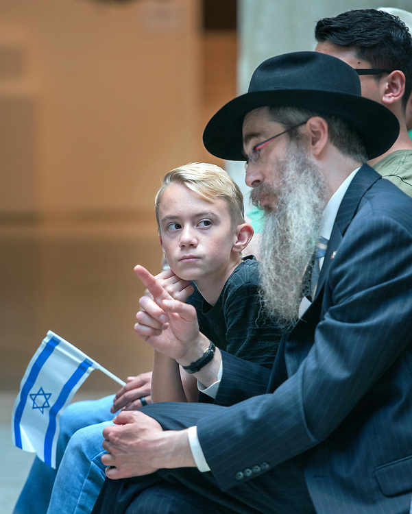 em060717a/a/Ari Rosenmader, 13, listens to Rabbi Berel Levertov, with the Santa Fe Jewish Center, while they watch a live stream of ceremonies commemorating the 50th anniversary of the reunification of Jerusalem. This ceremony was held in the Rotunda of the State Capitol in Santa Fe Wednesday June 7, 2017. The events they were streaming were from Jerusalem and Washington D.C. Around 40 people including some state legislators attended the event that was organized by the Santa Fe Jewish Center and the Jewish Federation.  (Eddie Moore/Albuquerque Journal)