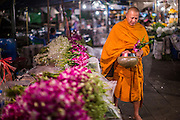 19 OCTOBER 2012 - BANGKOK, THAILAND:  A Buddhist monk walks through the Bangkok Flower Market on his morning rounds collecting alms. The Bangkok Flower Market (Pak Klong Talad) is the biggest wholesale and retail fresh flower market in Bangkok.  The market is busiest between 3:30AM and 6AM.      PHOTO BY JACK KURTZ
