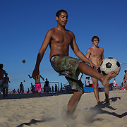 Locals practice foot  volley, a hybrid game combining beach volley ball and football at Ipanema beach, Rio de Janeiro,  Brazil. 4th July 2010. Photo Tim Clayton..