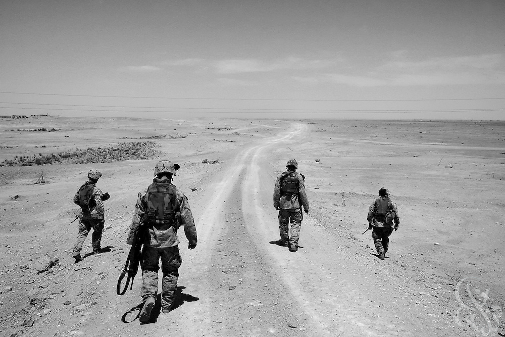 AL-QAIM, IRAQ - MAY 18, 2005:  U.S. Regimental Combat Team 2 Marines search a remote desert road near the Syrian border for mines and roadside bombs during a routine mission to a radio communication tower and back May 18, 2005 near the Iraqi city of Al-Qaim.  The U.S. military suspects that the Syrian-Iraq  border has  become an important transit point for foreign fighters and suicide bombers heading in to Iraq, and have recently conducted operations intended to stem the flow. (Photo by Scott Nelson/WPN)