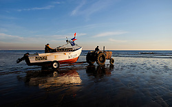 © Licensed to London News Pictures.12/06/15<br /> Saltburn by the Sea, England<br /> <br /> The last remaining commercial fishing boat in Saltburn, Ellen, is driven down to the shore line before being launched by her crew as dawn breaks over the beach.<br /> <br /> Photo credit : Ian Forsyth/LNP