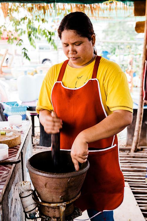 Making som tam (papaya salad) with saak (mortar) and krok (pestle), Udon Thani