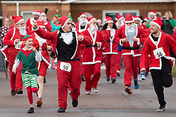© Licensed to London News Pictures. 11/12/2016. Nuneaton, Warwickshire, UK. Runners dressed as Santas and Elfs took to th streets today to raise money for the Mary Ann Evans Hospice in Nuneaton. The annual 5K Santa dash started and finished at the George Eliott Hospital. Photo credit: Dave Warren/LNP