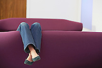 Woman Relaxing upside down on Sofa low section