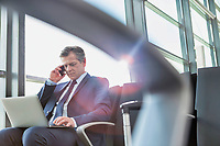 Mature attractive businessman talking on smartphone while sitting and working with his laptop before boarding in airport