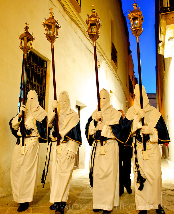 A group of four penitents march in  a row