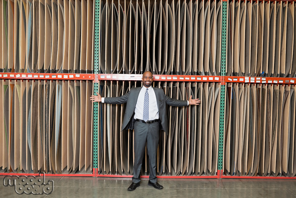 Portrait of happy African American businessman standing arms outstretched in front of thin veneer sheets