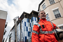"""© Licensed to London News Pictures. 16/11/2019. Bolton, UK. Assistant County Fire Officer DAVE KEELAN at a press conference at the scene as firefighters work after a fire broke out overnight (15th/16th November 2019) at a block of flats known as """" The Cube """" , in Bolton Town Centre . At least two people are known to have been treated by paramedics at the scene of the six-story block , which is occupied by students of the University of Bolton . Photo credit: Joel Goodman/LNP"""