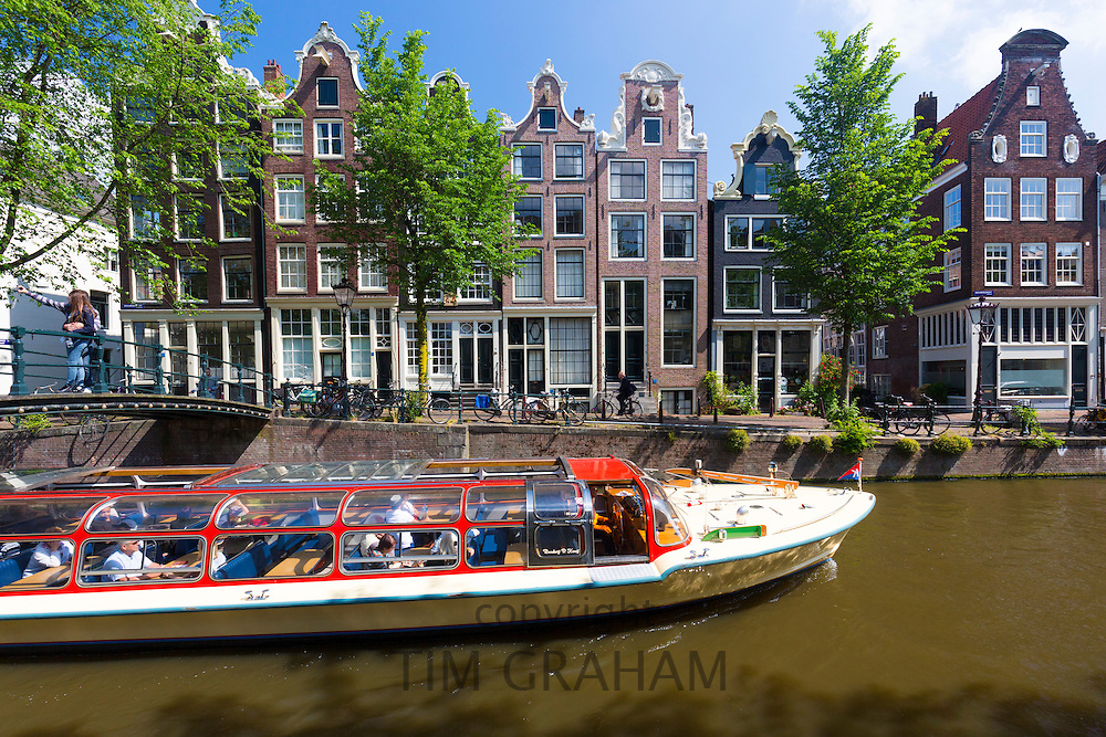 Canal tour barge cruise boat  takes tourists group by canalside gabled houses - Dutch gables - Brouwersgracht, Amsterdam, Holland