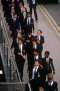 A group of schoolboys from the City of London school in central London, visit a financial institution as part of their education course work. Wearing the jackets and trousers with the dark colours of their college, the boys look to be in high-spirits as they walk along a street in the capital. Looking upwards to where the tall banks and insurance institutions may tempt them to seek careers in the Square Mile - London's oldest quarter and financial district. The City of London School (CLS) or City is a boys' independent day school on the banks of the River Thames in the City of London, England  founded by a private Act of Parliament in 1834, following events starting from a bequest of land by John Carpenter, Town Clerk of London in 1442, for four poor children in the City of London.