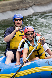 Family paddling down river in inflatable canoe