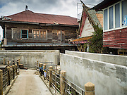 05 OCTOBER 2015 - BANGKOK, THAILAND: A new sea wall, to prevent flooding from the Chao Phraya River, in fronts of homes in the Wat Kalayanamit neighborhood. The homes are scheduled to be torn down. Fifty-four homes around Wat Kalayanamit, a historic Buddhist temple on the Chao Phraya River in the Thonburi section of Bangkok, are being razed and the residents evicted to make way for new development at the temple. The abbot of the temple said he was evicting the residents, who have lived on the temple grounds for generations, because their homes are unsafe and because he wants to improve the temple grounds. The evictions are a part of a Bangkok trend, especially along the Chao Phraya River and BTS light rail lines. Low income people are being evicted from their long time homes to make way for urban renewal.        PHOTO BY JACK KURTZ