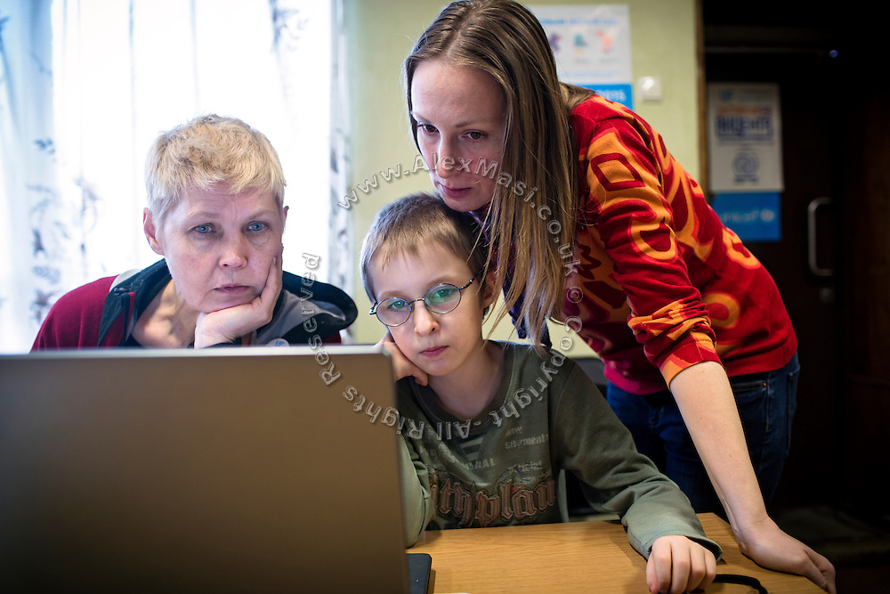 Using a computer, Marina Rassokha, 50, (left) of 'Ukrainian Frontiers', is reviewing some video made by Yaroslav, 10, as his mother Olga, 36, is overlooking while inside a community meeting place in support of internally displaced persons. (IDPs) Yeroslav is taking part to the UNICEF-sponsored One Minute Junior project for internally displaced persons (IDPs), carried out by the local NGO 'Ukrainian Frontiers' in the city of Kharkiv, the country's second-largest, in the east. The conflict between Ukrainian army and Russia-backed separatists nearby, in the Donbass region, have left more than 10000 dead since April 2014, including over 1000 since the shaky Minsk II ceasefire came into effect in February 2015. The approximate number of people displaced by the conflict is 1.4 million as of August 2015. Yeroslav's mother, Olga, is also a participant to a different project of 'Ukrainian Frontiers', called 'Self-Employment', first as a beneficiary, and now as a paid hotline coordinator for people seeking jobs and formation courses.