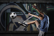 A young boy plays street soccer against a graffiti covered wall - with dramatic lighting and subdued colors - EXCLUSIVELY AVAILABLE on ALAMY http://www.alamy.com/stock-photo-a-young-boy-plays-street-soccer-against-a-graffiti-covered-wall-with-67184265.html