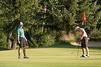 A male golfer putts on the 12th green at Whistler Golf Course, while his partner looks on. Whistler, BC Canada.
