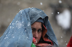 61023455<br /> An Afghan refugee woman waits to receive winter relief supplies donated by German government at a refugee camp during snowfall in Kabul, Afghanistan, on Feb. 6, 2014. Around 146 refugee families received winter relief supplies on Thursday, Afghanistan. Thursday, 6th February 2014. Picture by  imago / i-Images<br /> UK ONLY
