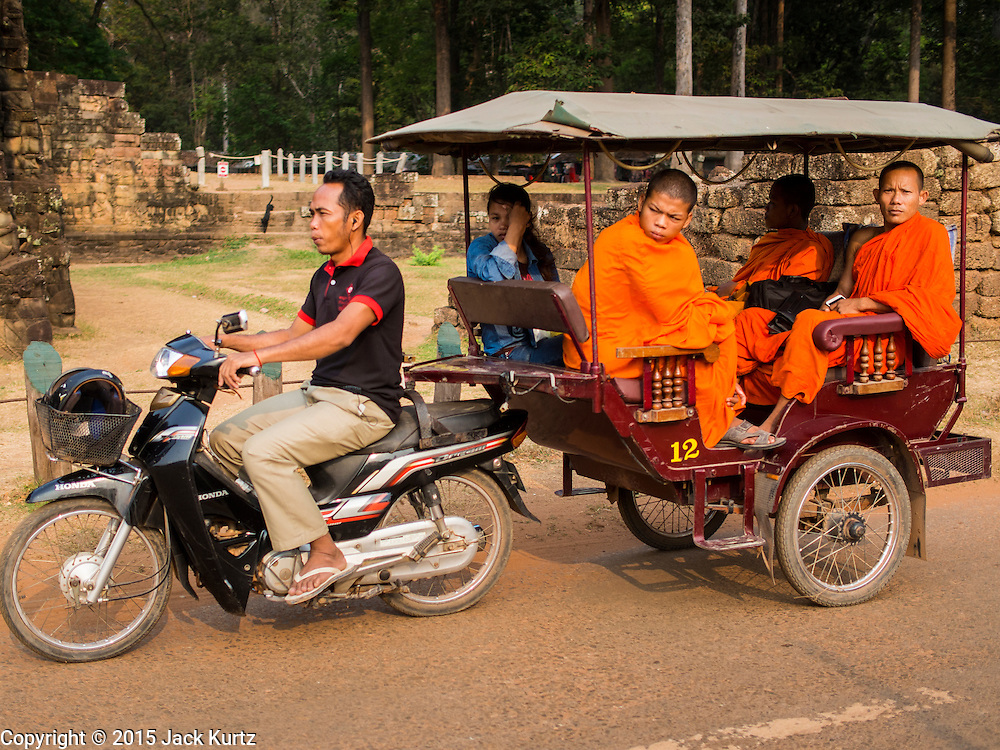 """14 MARCH 2105 - SIEM REAP, SIEM REAP, CAMBODIA: Buddhist monks use a tuk-tuk (three wheeled taxi) in Angkor Thom, a part of the Angkor Wat complex. The area known as """"Angkor Wat"""" is a sprawling collection of archeological ruins and temples. The area was developed by ancient Khmer (Cambodian) Kings starting as early as 1150 CE and renovated and expanded around 1180CE by Jayavarman VII. Angkor Wat is now considered the seventh wonder of the world and is Cambodia's most important tourist attraction.   PHOTO BY JACK KURTZ"""