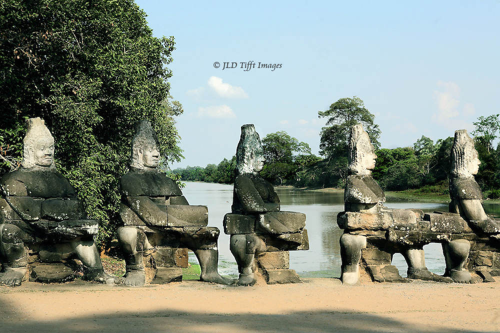 Naga balustrade, Angkor Thom.  Side view of the demons (asuras) holding the body of the Naga (cobra), visible in pieces held by each figure.  City moat beyond.  Some of the heads are modern replacements.  The figures hold a squatting position as they pull o the body of the serpent as they churn the sea of milk.