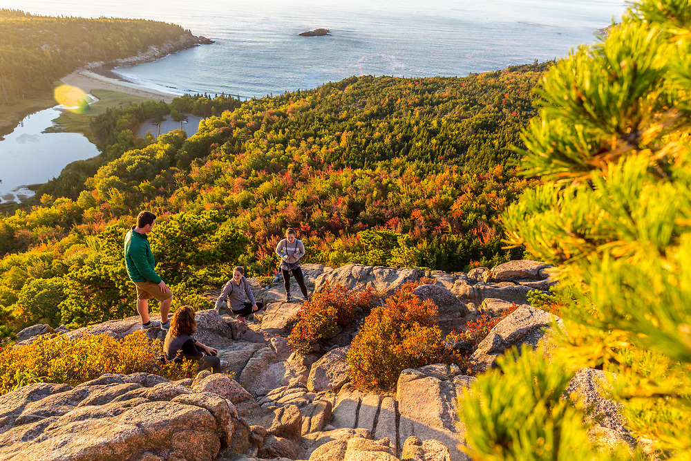 """Hikers take a break on """"The Beehive"""" in fall in Maine's Acadia National Park."""