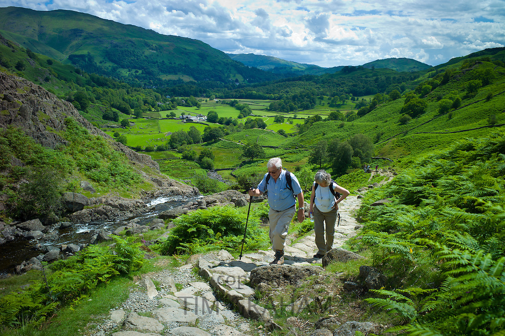 Tourists hill climbing on nature trail in lakeland countryside at Easedale in the Lake District National Park, Cumbria, UK