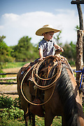 Matteo Campello, grandson to Carl White, sits on a horse waiting on his Uncle Rylan to finish saddling the other horses.