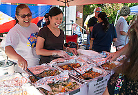 Liza Kelleher and GieGie Marrone serve up a variety of specialties from the Phillipines during Saturday's Multi Cultural Festival in downtown Laconia.  (Karen Bobotas/for the Laconia Daily Sun)