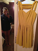 Blonde becomes internet celebrity after posting dress on eBay without realising she was also in the picture - NAKED from the waist down<br /> <br /> A woman who listed her dress on eBay has become an instant celebrity after accidentally including a naked view of herself in the website listing.<br /> The blonde, identified only by the user ID as 'sugart*t-2' hung the mustard yellow skater dress by ASOS on her wardrobe door to photograph it for listing.<br /> But she failed to notice her own reflection in the door mirror, camera in hand, and in just a black bra and no knickers.<br /> <br /> Bargain-hunters spotted her at the margin of the eBay picture and it was immediately shared on Twitter with the hash tag #ebayyellowskaterdress. Within hours it had gone viral.<br /> Embarrassed eBay managers pulled the entry before the sale ended, but an unabashed Sugart*t-2, who lives in Oxfordshire, has now relisted the dress with a similarly-posed picture - only this time it shows her - just about covered up - in a dark Nike top.<br /> <br /> The listing now reads: 'Asos yellow skater dress size 10, 2nd time round!! a MUST HAVE!!<br /> 'As seen by thousands. Never worn naked. Needs a good home.'<br /> <br /> Bizarrely the listing has caused a stir among eBay users. Originally listed at £15.99, the dress has received more than 130 bids and with two days to go had reached more than £153,000.<br /> The sale is due to finish just after 10pm on Thursday.<br /> The picture brought mixed reaction on internet forums. One user commented: 'It is a shocking dress'.<br /> <br /> Photo shows: Bit more demure: She re-listed the item on eBay and this time covered up with a black coat. It has attracted bids of £153, 911 so far<br /> ©Exclusivepix