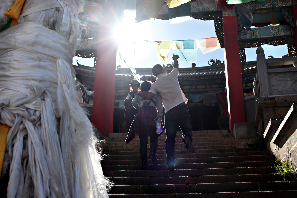 Chinese tourists climb the stairs to a temple in old-town Shangri-la, Yunnan, China; September, 2013.