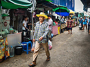 21 SEPTEMBER 2016 - BANGKOK, THAILAND: People walk past the construction site now occupying the land that used to be the Bang Chak Market. A street market is on the street in front of the construction site. The market closed permanently on January 4, 2016. The Bang Chak Market served the community around Sois 91-97 on Sukhumvit Road in the Bangkok suburbs. Bangkok city authorities put up notices in late November 2015 that the market would be closed by January 1, 2016 and redevelopment would start shortly after that. Market vendors said condominiums are being built on the land.      PHOTO BY JACK KURTZ