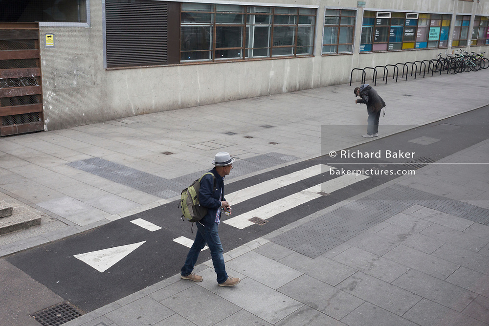 Unknown to each other, two men are separated by the Elephant & Castle cycle lane, on 20th May 2019, in London, England.